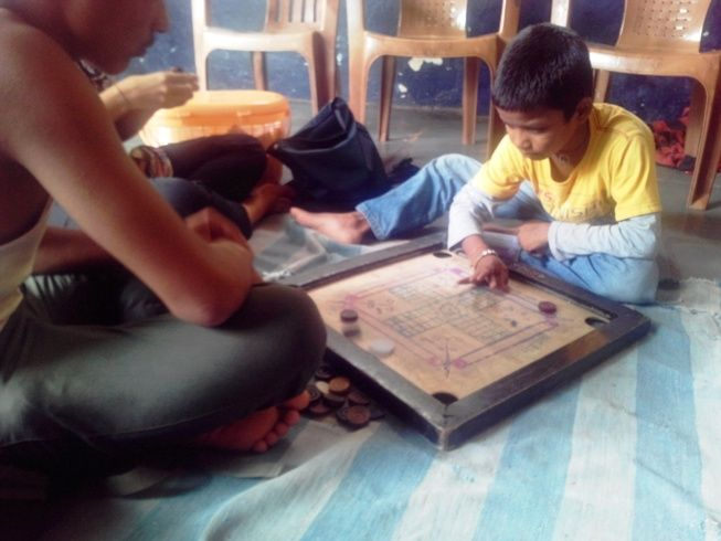 Volunteers playing carrom ( a kind of game) with the children in a rescue center. All the children rescued from a factory, where they were doing child labour!