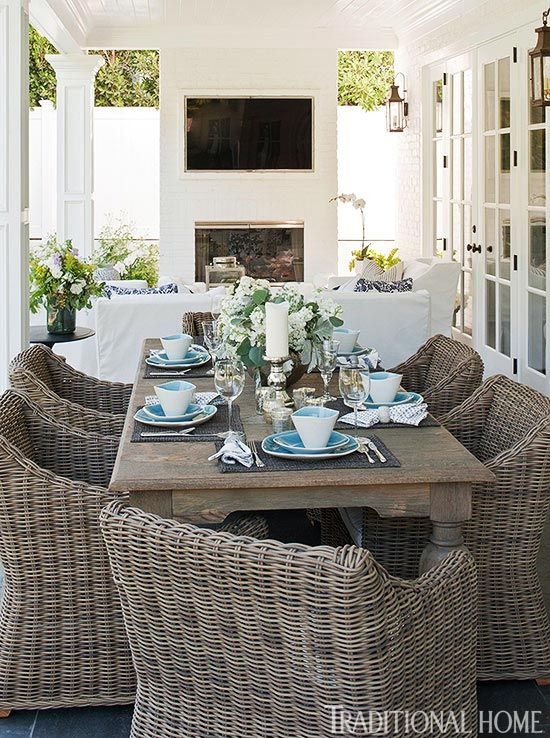 fireplace w/ tv, white slipcovered seating, wicker dining chairs all make for a great place to hang out on the porch.