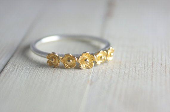 Je zult stralen elegantie met deze sterling zilver en goud bloem ring van Ted en Mag. Custom handgemaakt in fascinerende detail, het is echt een werk van draagbare kunst. Een reeks van delicaat gouden bloemen zitten op een aangepaste handmade sterling zilveren band in een adembenemende weergave van ontwerp. Is het zeker tot een nietje in uw sieraden collectie als Pools zal het toevoegen aan uw outfit net toen u het meest nodig hebben. Het maakt ook een geweldig cadeau voor een vriend nodig…
