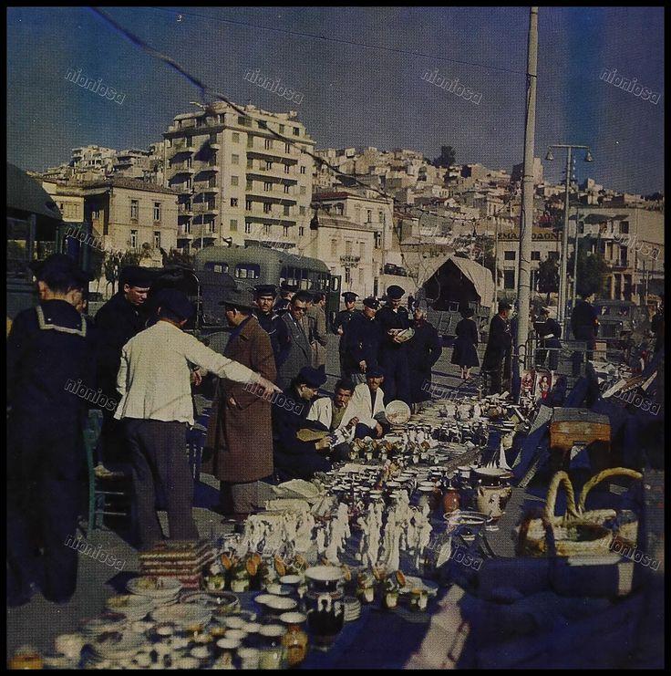 Μικροπωλητές επιδεικνύουν την πραμάτεια τους σε αμερικανούς ναύτες στο Πασαλιμάνι, 1957-1958.
