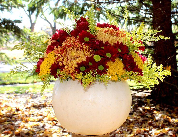 Arreglo floral en zapallo blanco con crisantemos y solidago,