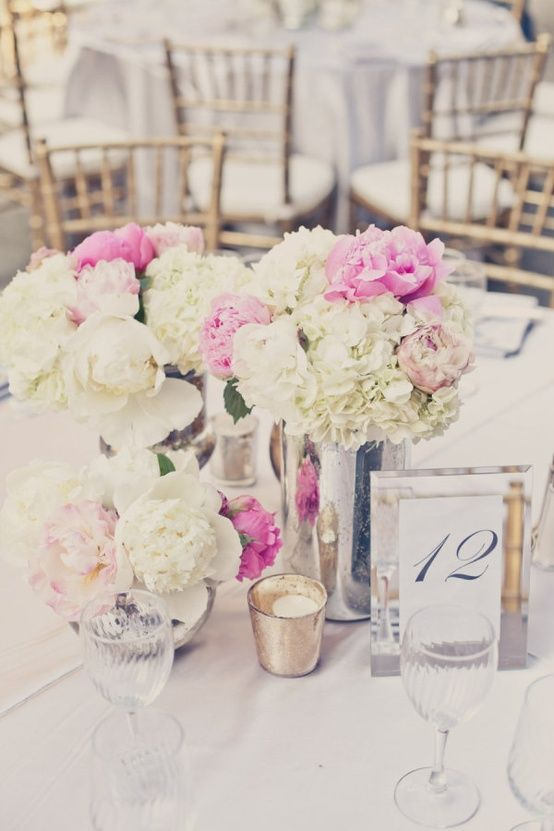 Some of the centerpieces will be clusters of skinny cylinder vases at varied heights filled with white hydrangeas, pink peonies, and pink sweet peas surrounded by varied heights of silver mercury glass votives.