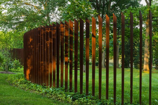 The sculptural quality of open fencing is amply demonstrated in this custom-made, curvaceous example, made of 300 Cor-Ten noncorroding steel alloy blades, angle cut at the top and set into a 3-foot concrete base 8 inches apart.