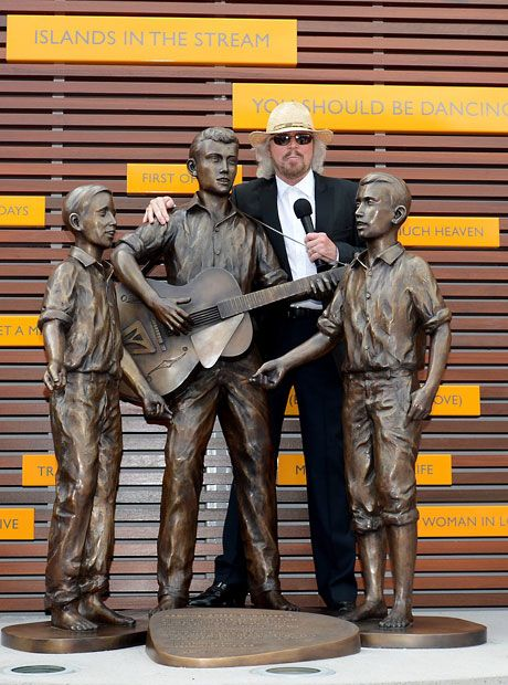 Barry Gibb stands with a sculpture of himself and his brothers Robin and Maurice at the official opening of Bee Gee Way in Redcliffe, northern Brisbane, Australia