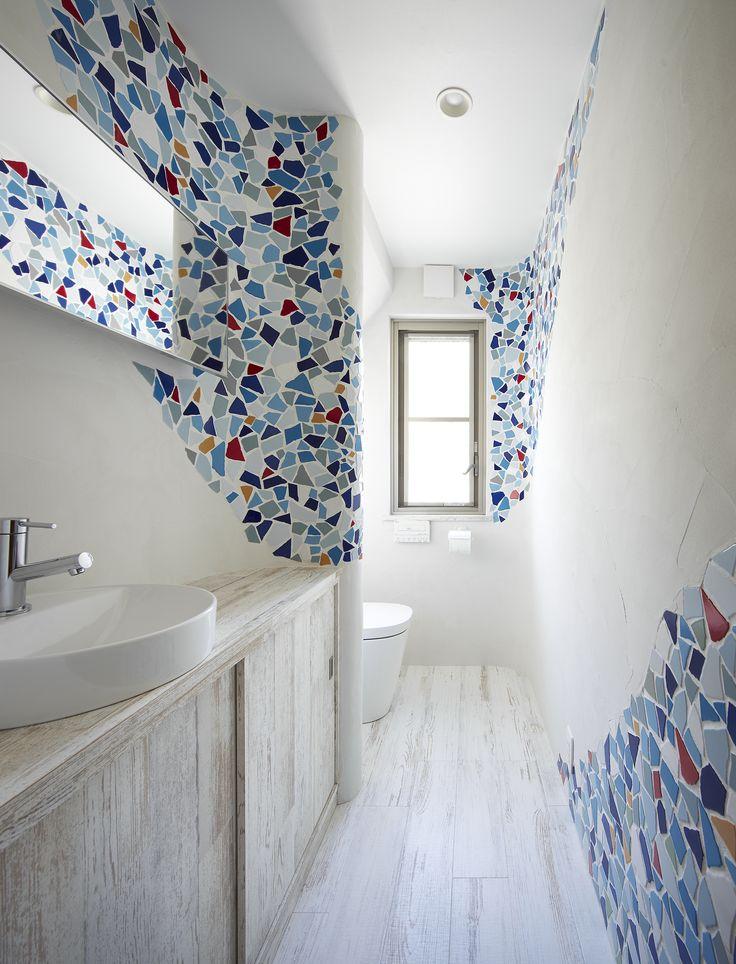 浴室の水漏れを機に水廻り設備の交換のリフォームをしました。2階トイレは海外勤務の際に一目惚れされた曲線とタイルを用いたスペイン風の空間に一新。壁をふかして曲面をつくりクラッシュタイルを流れるように配置。タイルの厚さに合わせて珪藻土で仕上げることでなめらかな曲面をつくり出しています。お手入れのしやすさにも配慮して床は樹脂タイル張り、手洗いカウンターは傷や水に強い木目調のメラミン化粧板の造作です。間接照明も設置し、昼は窓からの光、夜は照明の演出を楽しみながらくつろぐ、極上のプライベートスペースとなっています。手洗いカウンターの幅いっぱいに設けた鏡の効果も効いています。