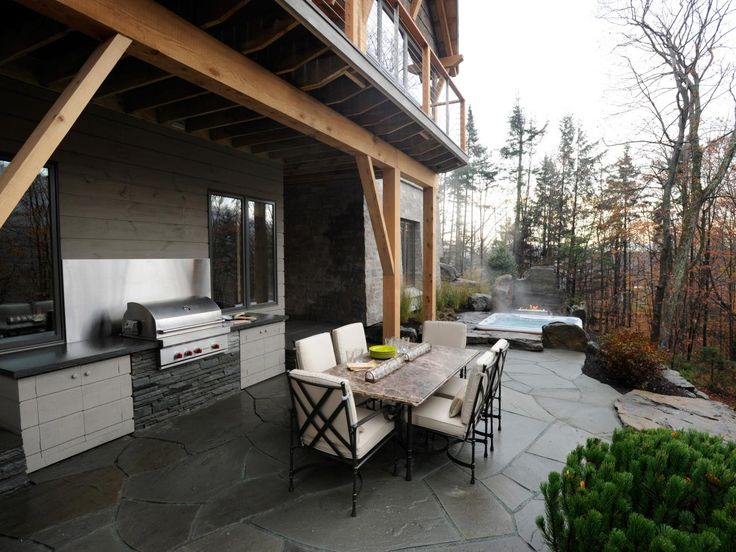 The lower level terrace is a top-notch entertaining spot featuring a grilling station, hot tub and outdoor dining table.