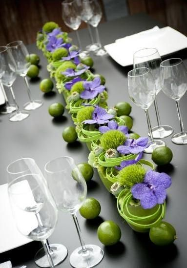 Egyedi, lila-zöld esküvői asztaldísz lime-okkal.