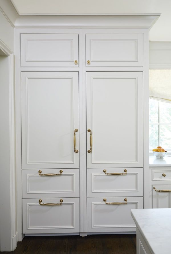 "Cantley & Company ""The SubZero refrigerator and freezer are beautifully integrated behind custom cabinet doors,"" says Cyndy. ""Using brass pulls is so much prettier than refrigeration of the past."" This is Cantley & Company's custom English-style inset door with Kent Moulding painted a soft, custom white."