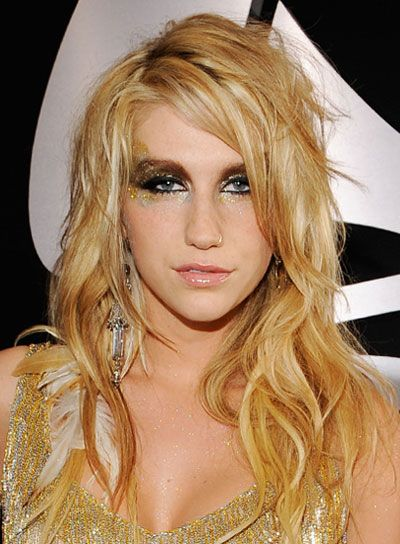 Ke$ha Blonde, Wavy, Tousled Hairstyle  1. Forget about washing your hair, this look works best on dirtier hair. Rub a large dallop of texturizing mousse through day-old hair and braid it overnight.   2. The next morning, take out your braids and spritz your waves with salt spray. Use your hands to scrunch them and let them dry.   3. Spritz your roots with some volumizing spray and blow dry while lifting hair at the roots to add sexy volume.