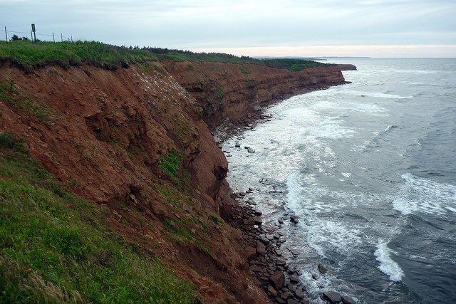 The red dirt of PEI late afternoon with small waves.