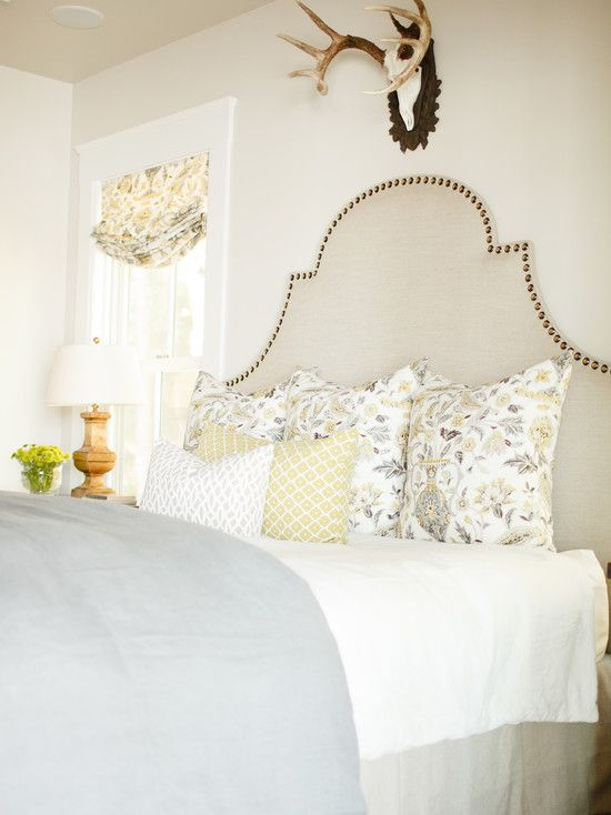 source: Caitlin Creer Interiors   Arched linen upholstered headboard with nailhead trim. Bed layered with gray and yellow floral pillows, a yellow and white geometric pillow and small gray and white geometric pillow. Ivory bed linens pair with a gray folded coverlet at the foot of the bed. In front of the sash windows stands a nightstand with wooden balustrade lamp. Pale tan colored walls