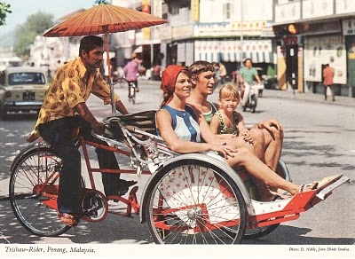 Here a trishaw rider pedals a family of foreign tourist around the not- so busy street of Penang, Malaysia. (in the 1970's)