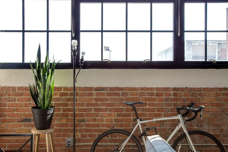 The apartment features many industrial elements, including exposed brick and exposed piping in the ceiling. Nicole and Dave celebrate and echo this architectural style with their decor. IKEA SKOGSTA stool with a plant from Home Depot on top.