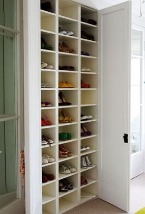 This floor-to-ceiling shoe shelf hides neatly behind double doors. The white shelves reflect light into the dark cubbies, making every pair easy to see.