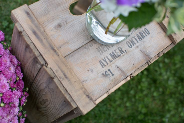 Old wooden crate used as a stand for flower jar at tent wedding in Aylmer