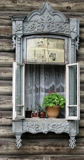 An intricately designed window on a simple wooden house.