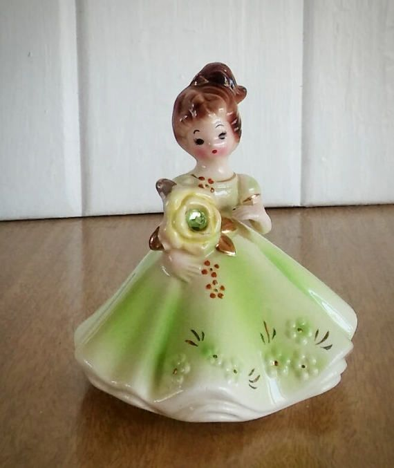 Josef Originals August with Peridot colored stone. Base is stamped with paper sticker; Japan still attached.  Minimal wearing on the bottom. Overall good condition. No chips, cracks or repairs.  What a beautiful figurine to give as a baby shower gift for the month of August. If you collectible this southern bells this is a pretty color to add to your collection. She does have some noted crazing due to her age. **See pictures for closer details**.  Measurements: Height: 4 ¼ inches Base…
