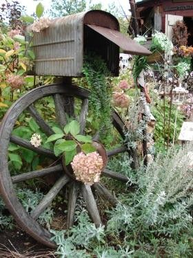 Decorative wagon wheel and mailbox for garden gloves and tools.