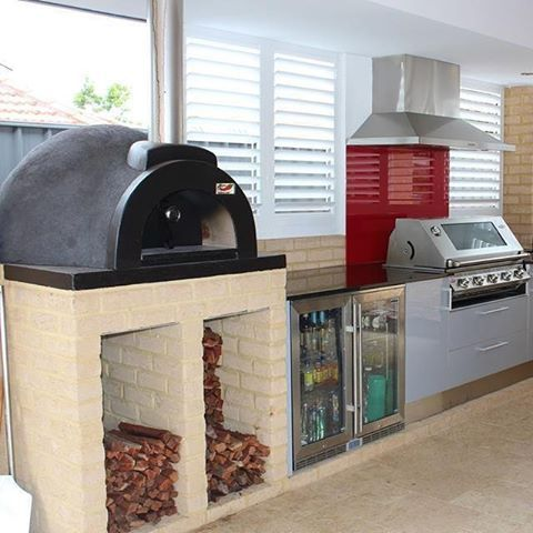 Love this beautiful indoor kitchen we've setup featuring the Alfresco WoodFired Pizza Oven plus a BBQ & indoor fridge from www.sydneyheaters.com.au #outdoorkitchensandbbqareas