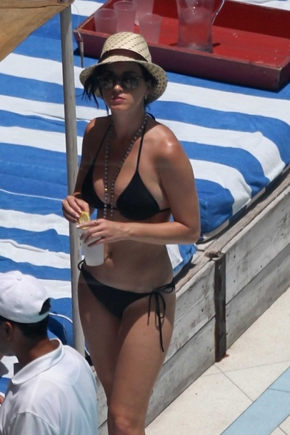Katy Perry shows some cleavage in a black triangle bikini top at the Soho Beach House pool in Miami Beach, FL. Katy wore a patterned fedora and brown Ray Ban sunglasses for an afternoon in the sun with family and friends. 7-26-2012