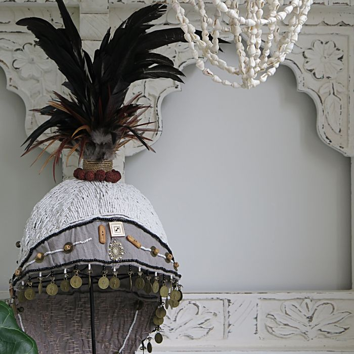 Tribal Warrior Hat: it doesn't get much more unique than this! This piece is crafted by hand in traditional Papuan style and each tiny bead is meticulously stitched in to place. Adorned with vintage coins and rooster feathers, this piece is sold inclusive of black metal stand and looks truly delectable placed on a console or dresser.