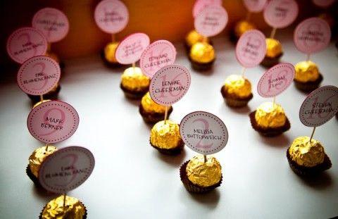 Sólo necesitas tantos bombones como invitados tengas. Imprime las etiquetas con los nombres de los comensales y pégalas en un palillo, luego sólo tendrás que pinchar el palillo en un bombón y colocarlo en el lugar que le corresponde en la mesa