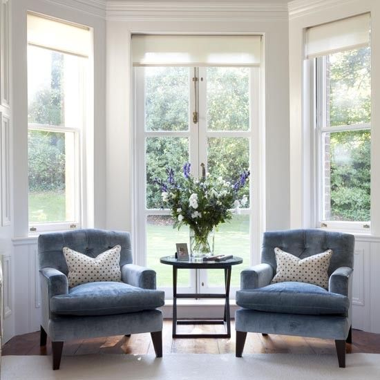 A pair of stylish armchairs and a side table provides the perfect reading spot.