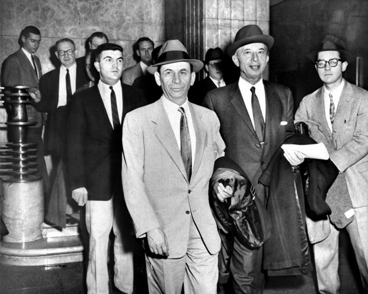 """The Jewish mob's elusive mastermind Meyer Lansky (center), known as the """"Mob's Accountant,"""" pulls a smug face as he walks with his lawyer Morris Polankoff in 1958."""