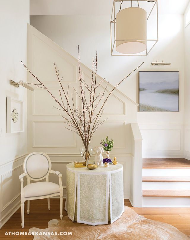 Designer Susan Walsh updated the front entry by trading an ironwork railing along the staircase for a paneled half wall that adds architectural interest. A skirted table softens the space and introduces guests to the home's pastel palette.  | Cottage Charmer | At Home in Arkansas | April 2016