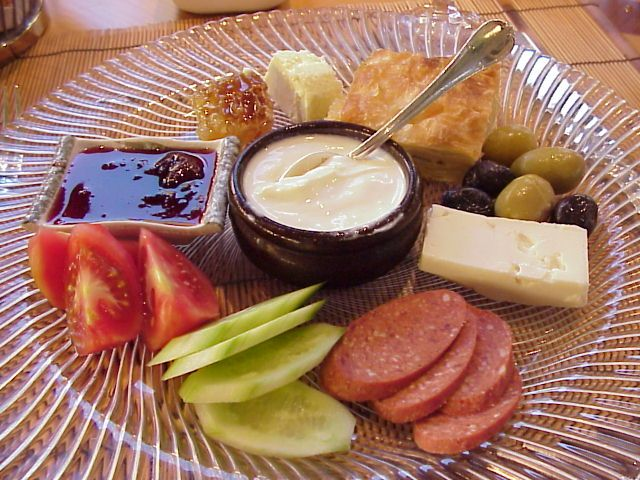Turkish Breakfast: white crusty bread or simit (the Turkish sesame bagel) served with butter, whole fruit preserves, honey, clotted cream, olives, peppers, tomatoes, cucumber, sausage and boiled eggs. Other popular morning dishes include savoury pastries and omelets. Breakfast is almost always served with Turkish tea or, less commonly, instant coffee.