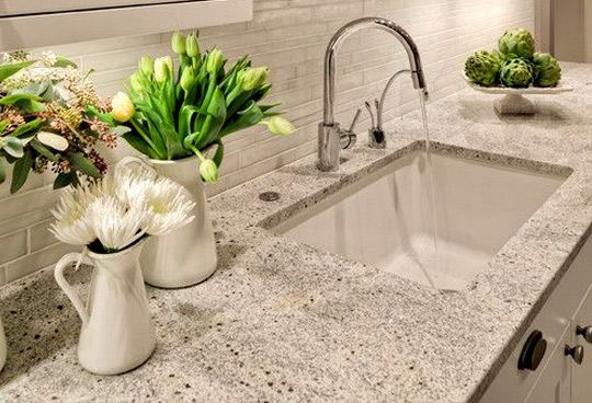 """Granite Pros: This ubiquitous, goes-with-everything surface is both hard and heat resistant--making it virtually impervious to scratches or stains. Cons: There aren't too many functionality cons. The real issue--as far as we're concerned--is that it's super safe, the """"vanilla"""" of countertops, if you will. You won't make any statements with granite"""