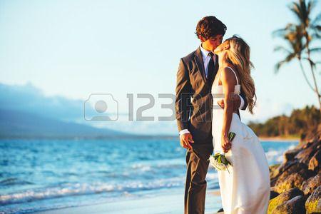 Romantic Couple de mariage embrassant sur la plage au coucher du soleil Banque d'images
