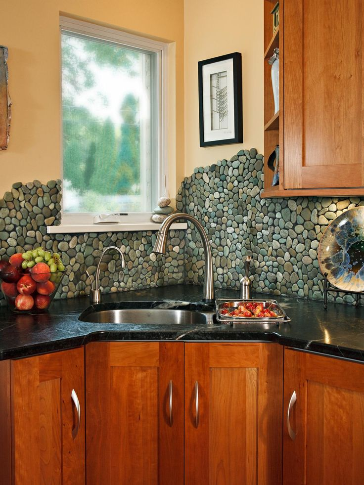 "Although the most common use of these river rock pebbles is actually shower floors, photo stylist Chris Walker and her husband came up with the idea of using them as a kitchen backsplash. They asked their kitchen designer John Petrie, CMKBD, president elect of the National Kitchen and Bath Association, to install it on the walls. ""The one-of-a-kind, free-flowing edges of the pebbles not only mimic the flow of soft teal veins in the dark green soapstone countertops,"" says Walker, ""but also…"