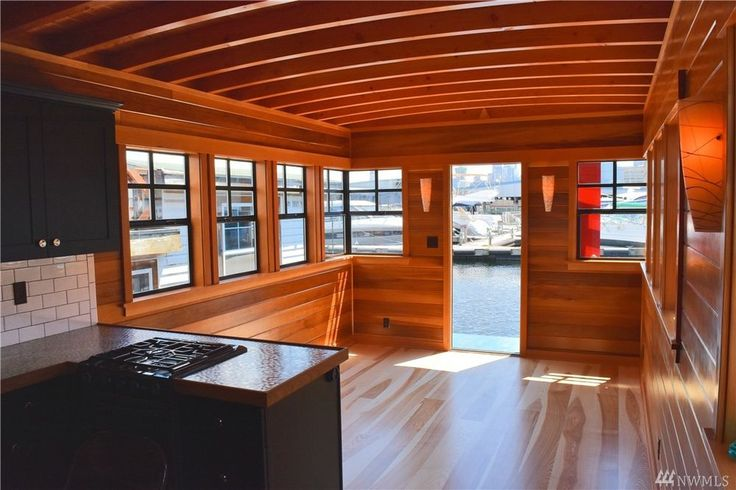 This tiny home has an all wood interior with exposed ceiling joists, wood paneled walls, corner windows, dark window mullions, and an open kitchen.