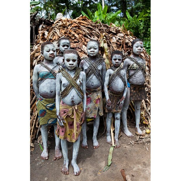 Africa |  Mbuti Pygmy girls painted in clay for the boys' circumcision ceremony pose for a picture in their village in the Ituri Forest on the Okapi Reserve (a UNESCO World Heritage Site) at Epulu   © Daniel Beltra