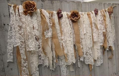 Shabby chic garland, hand tied with tattered tea stained and ivory lace, crepe, brocade and linen and accented with ivory and soft pink flowers. The flower stems are woven into the top to keep them se $159.00