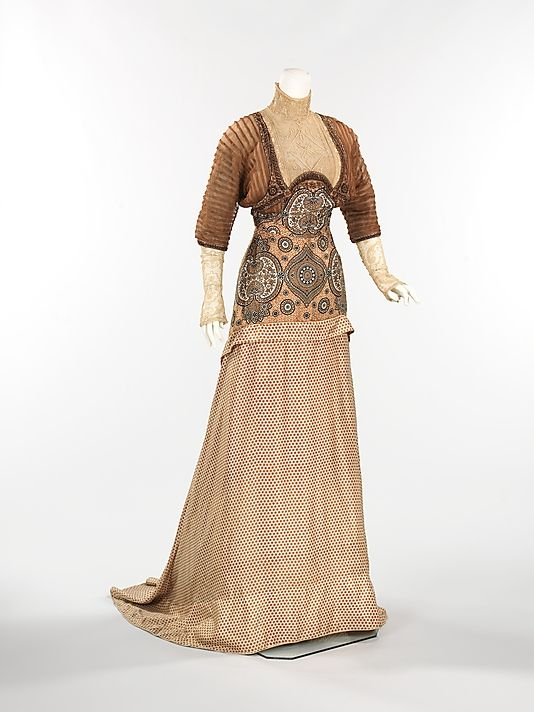 (1 of 2 photos) 1910 silk and linen evening dress by Weeks, French. Transitioning from the popular S-curve silhouette, this fashionable and eye-catching dress is more streamlined, with a slightly raised waist, introducing a more modern look. What is of most interest is the surprising combination of materials, using both polka dots and paisley patterns.