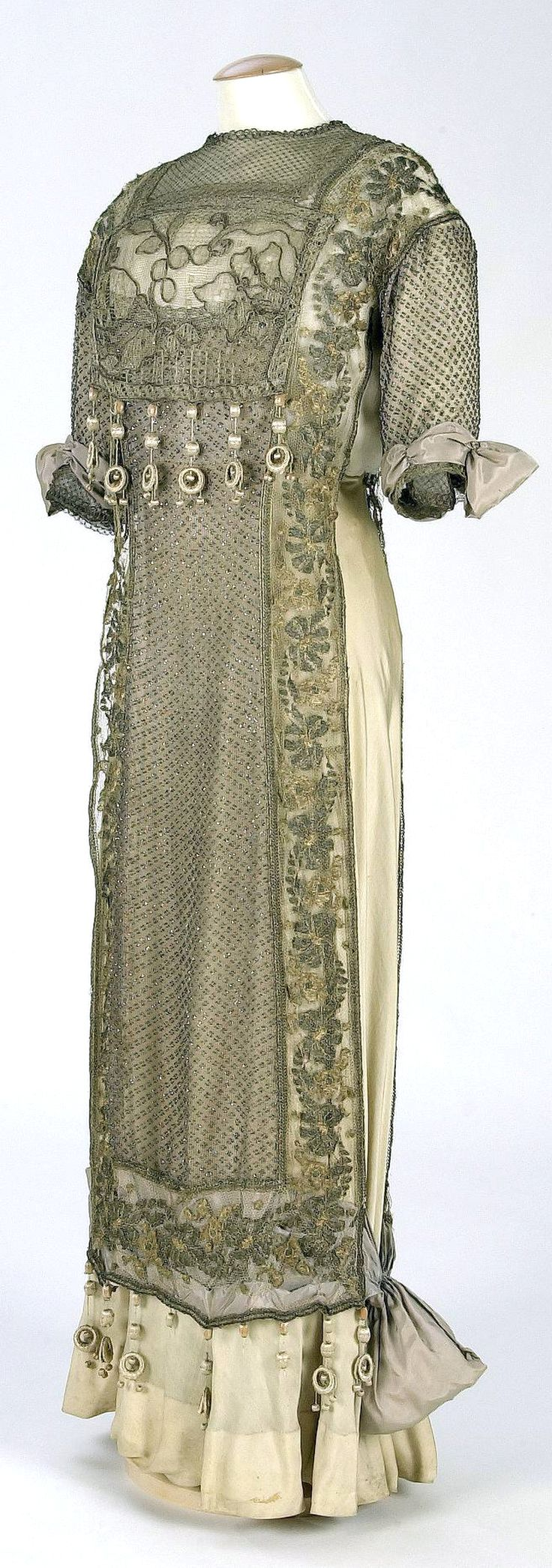 1910-1919 Day dress by Renaud & Cie, Barcelona. Cream-colored silk organza over silk satin with tunic overlay of tulle embroidered with beads and applications of metallic lace. Boned bodice. Textile Museum & Documentation Center, Terrassa, Spain. (IMATEX)