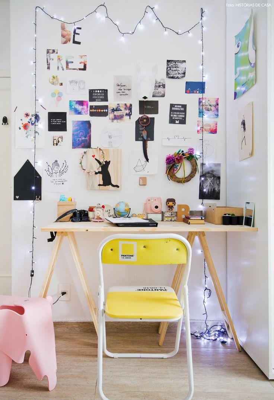 Cantinho de trabalho conta com escrivaninha com cavaletes e parede com referências.