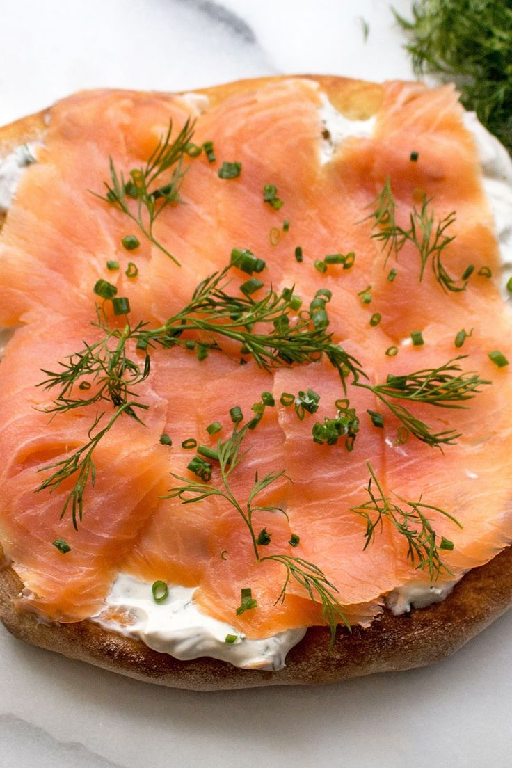 Recipe including course(s): Entrée; and ingredients: fresh chives, fresh dill, garlic, lemon juice, olive oil, pizza dough, red onion, salmon, shallots, sour cream