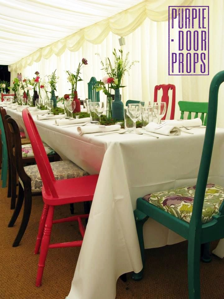 Purple Door Props mismatched colourful chairs for hire. Secret Garden Party with colourful flowers in bottles and moss table runners