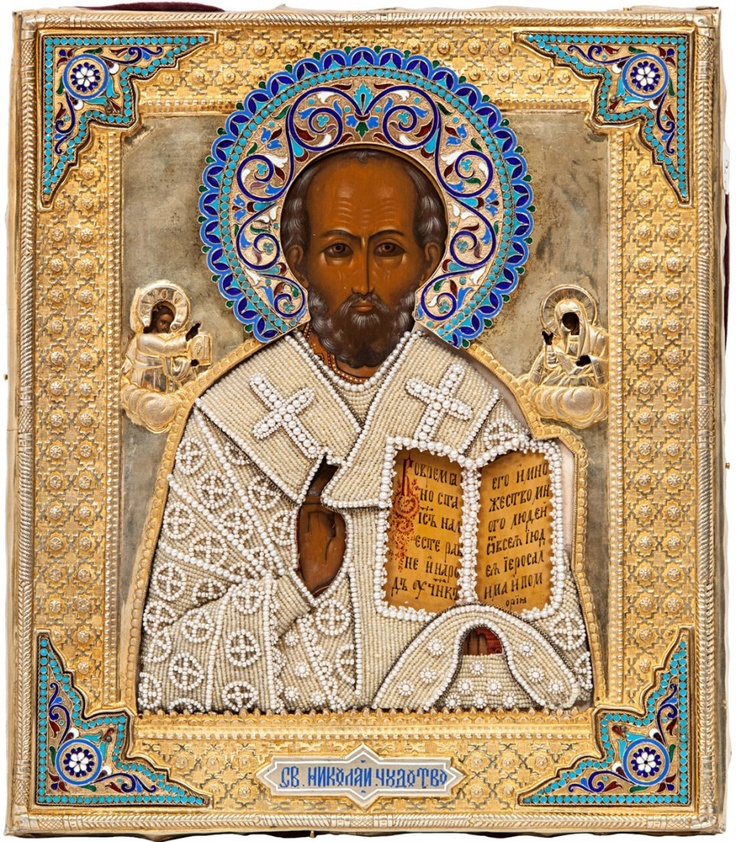 A RUSSIAN ICON OF SAINT NICHOLAS THE WONDERWORKER IN A GILT SILVER OKLAD WITH ENAMEL AND PEARLS, CYRILLIC MAKERS MARK PM, MOSCOW, CIRCA 1896, the gilt silver oklad ornately decorated with border of floral and geometric ornament, the spandrels applied with plaques of cloisonné enamel with vegetative designs, the halo with ornate polychrome cloisonné enamel, the vestments covered with a delicate pearl and seed bead insert.