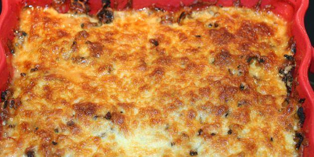 Ovnret med kartoffelskiver i bunden, porrer og hakket oksekød ovenpå, og smeltet ost på toppen.