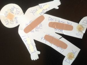 A paper cut-out of a person that has unkind phrases written on it has been torn to symbolize the effects of BULLYING. Read more on SCHOLASTIC.