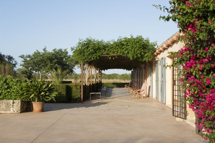 Mediterranean Rustic Exterior: Rocking chairs under a trellis in the landscaped exterior of an island home.