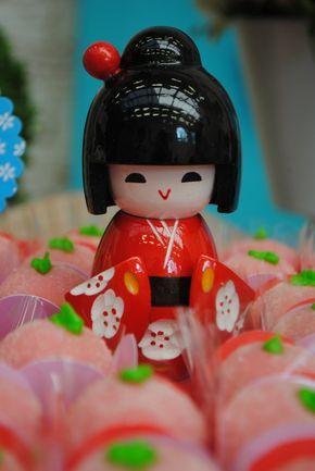Festa Kokeshi – De.Cuore. O primeiro ano dessa bonequinha japonesa teve decoração com o tema Kokeshi. Flores de cerejeira,  lanternas, ícones do japão, fotos e muitas bonecas fizeram parte dessa mesa do bolo criada nas cores rosa, azul e vermelho para esse aniversário de 1 ano de menina bastante criativo e diferente