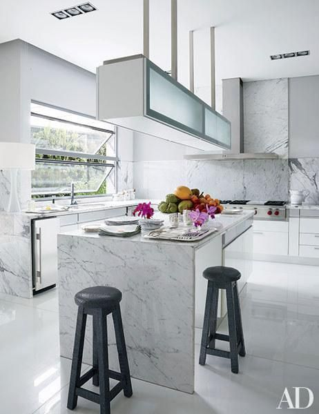 Handbag designer Nancy Gonzalez's Western Colombia apartment, designed with Jean-Louis Deniot, has a kitchen paved in marble and outfitted with a hood and a Wolf cooktop. Just a few decorative accessories on shelves and countertops let the smart mix of materials shine.