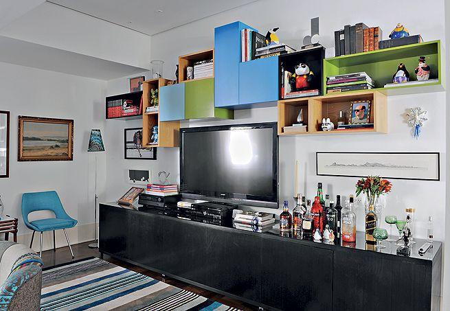 As cores preferidas do morador, o arquiteto Mario Celso Bernardes, repetem-se nos móveis, no tapete e na estante de módulos, projetada por ele e seu sócio, Junior. Instalada acima da TV no móvel de madeira ebanizada, ela guarda parte das coleções de pinguins e de toy art
