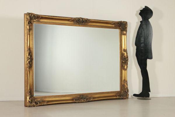 Grande specchiera in stile, intagli e trafori sugli angoli e nelle fasce. Specchio bisellato. Interamente dorata.