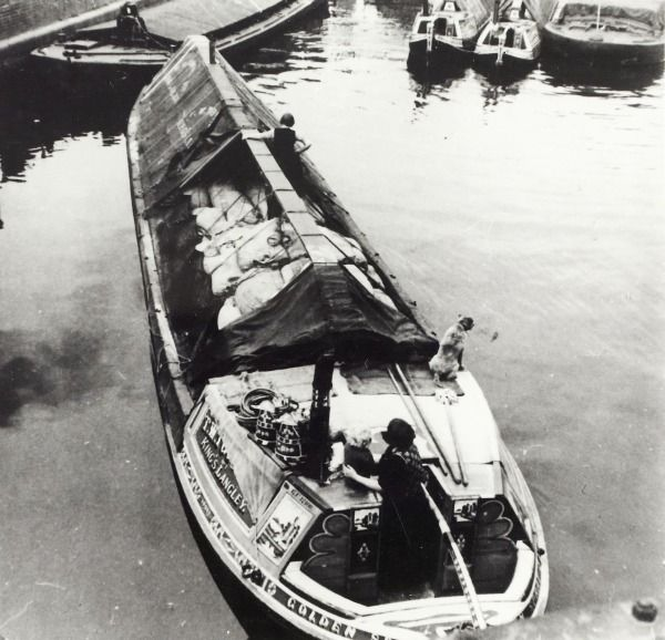 """Caption """"Black and white photograph taken by Cyril Arapoff, shows the stern of the Bushells built, T.W. Toovey owned decorated wide boat on the Grand Union Canal at Brentford. There is a boatwoman stood behind the cabin and a child sat on the cabin, with another boatwoman stood on goods in the hold. There is also a dog on the cabin. In the background the Fellows, Morton & Clayton Limiteed butties 'Foxton' and 'Evenlode' can be seen."""""""